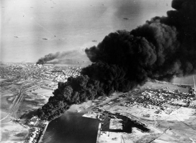 Smoke rises from oil tanks beside the Suez Canal hit during the initial Anglo-French assault on Port Said, 5 November 1956.jpg